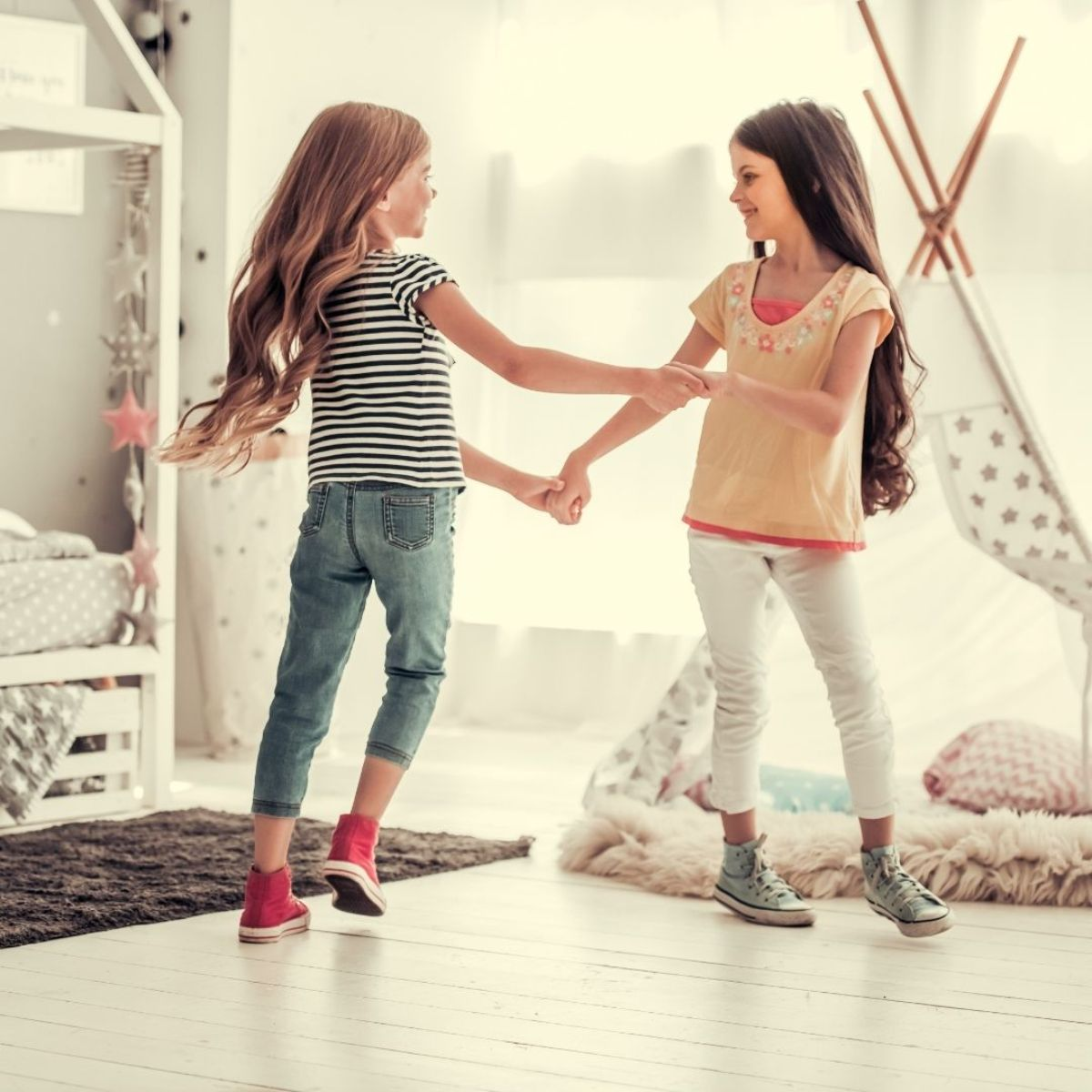 two girls dance around in a room holding hands in front of a teepee and bedframe