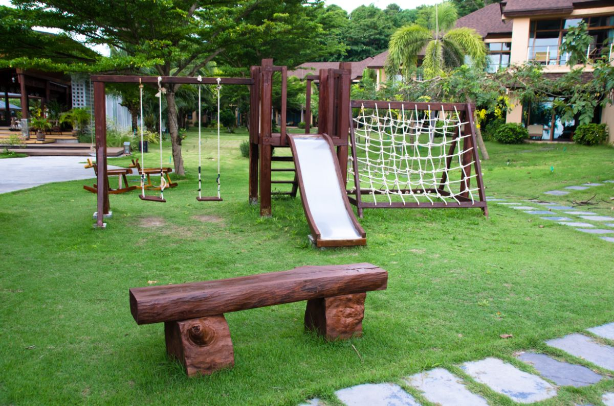 A photo of a play park with dark wooden play equipment. A slide, swings climbing net and bench. Sat on green grass with a path surrounding it