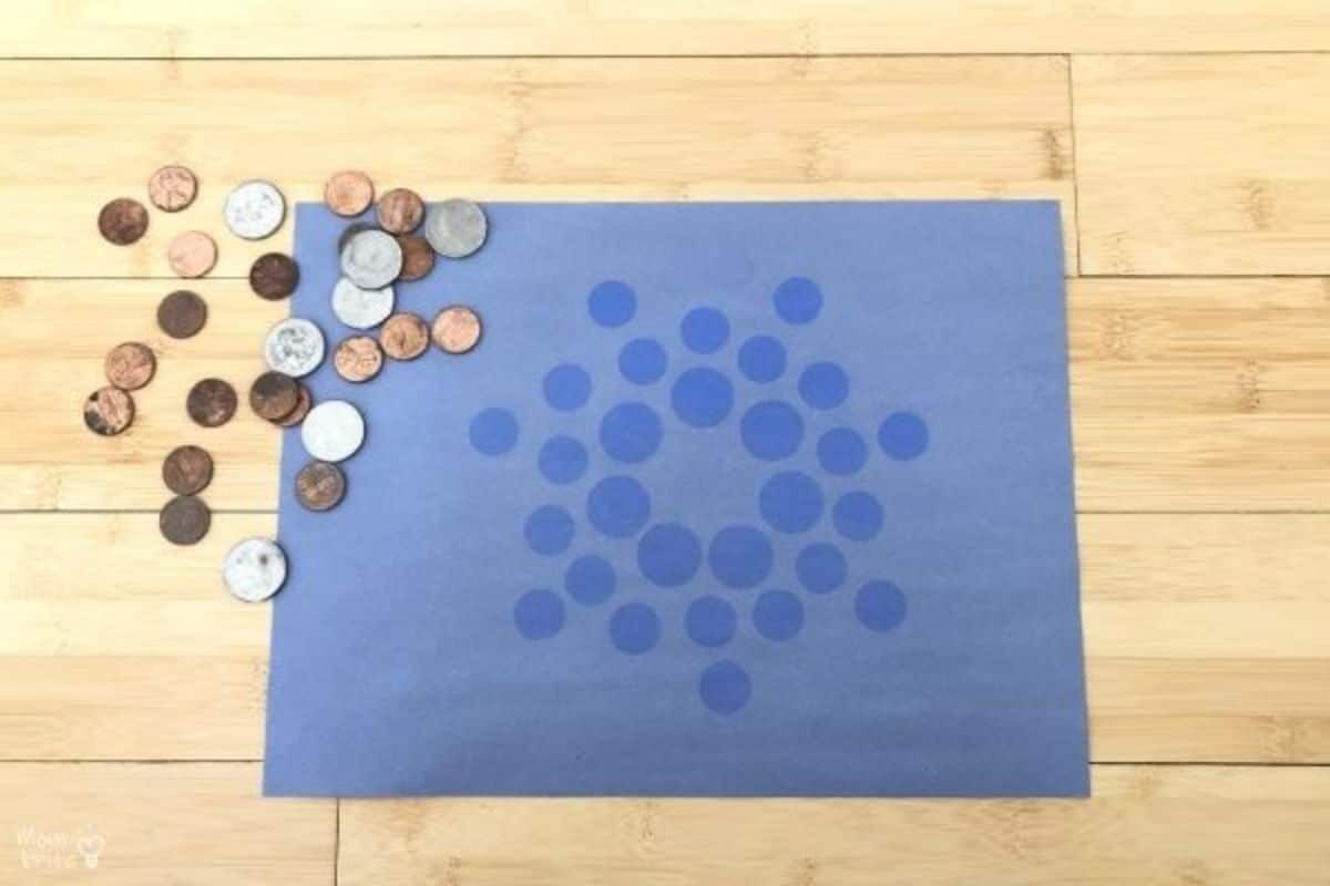 a blue sheet of scrapbook paper with darker circles on it. To the left is a pile of pennies