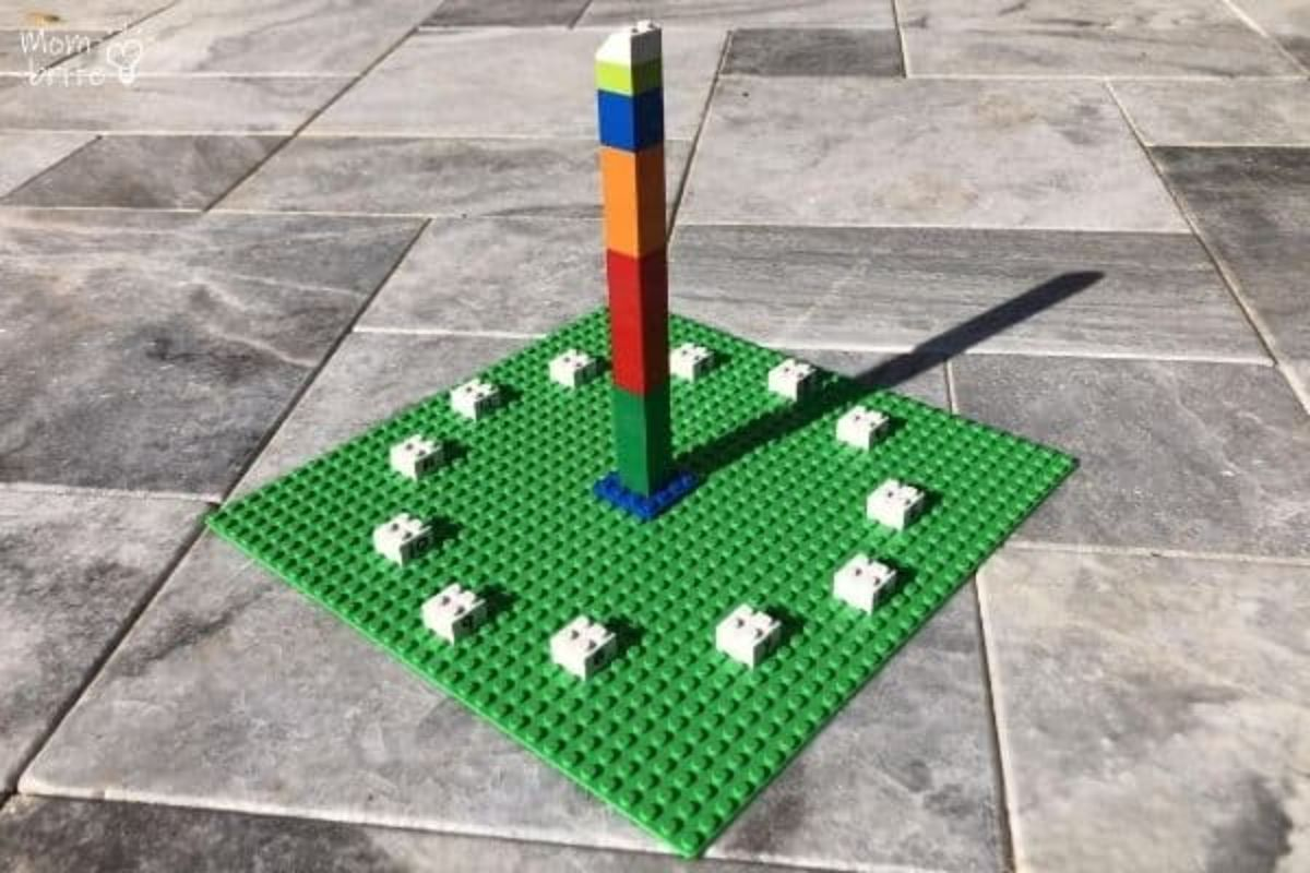 on a patio is a large green lego board with a tower in the middle and 12 white lego blocks arranged in a circle around it