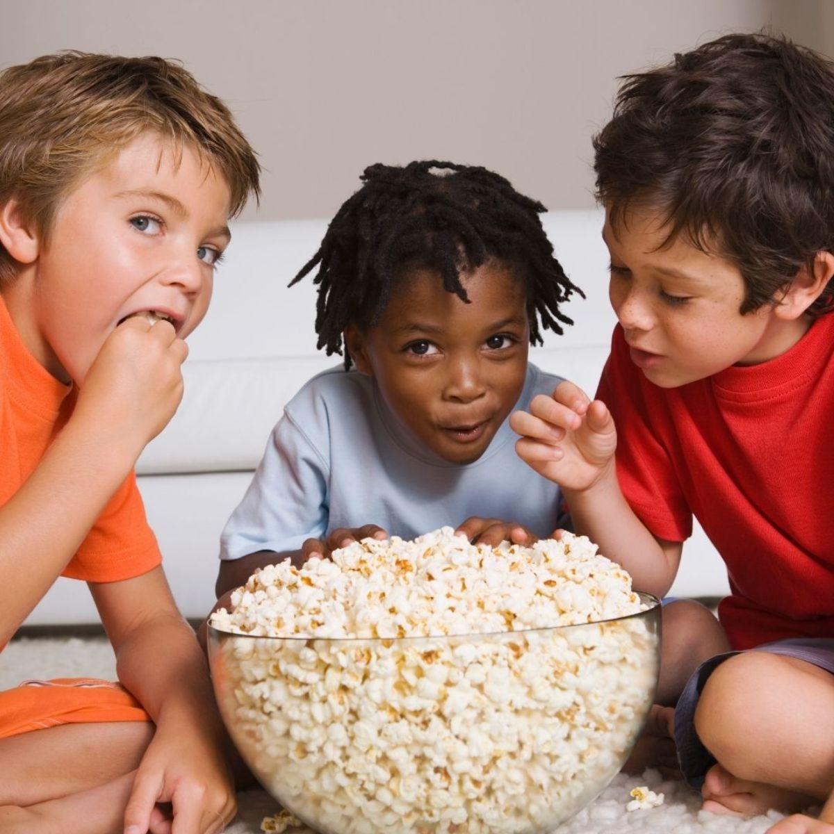 3 boys gather around a glass bowl full of popcorn