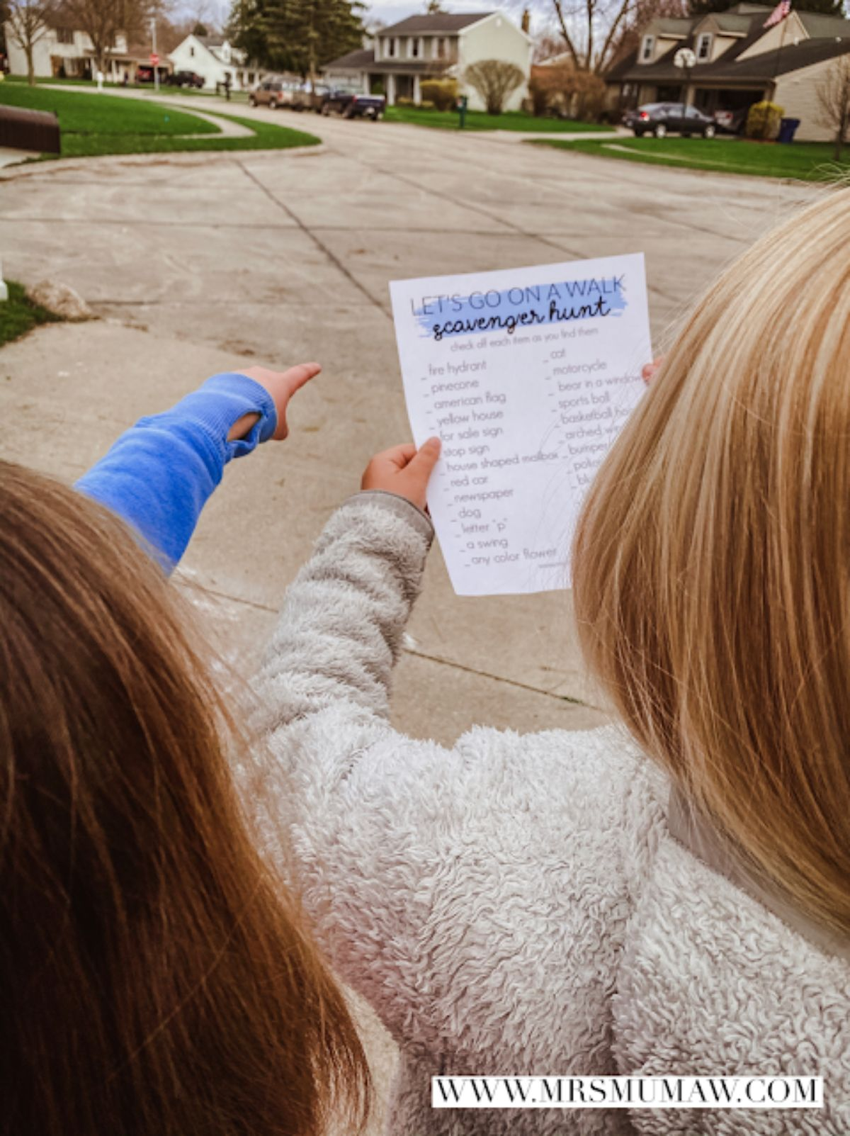 2 children point off into the distance as they are walking through a neighborhood residential street. One of them is holding a sheet of paper with writing on it