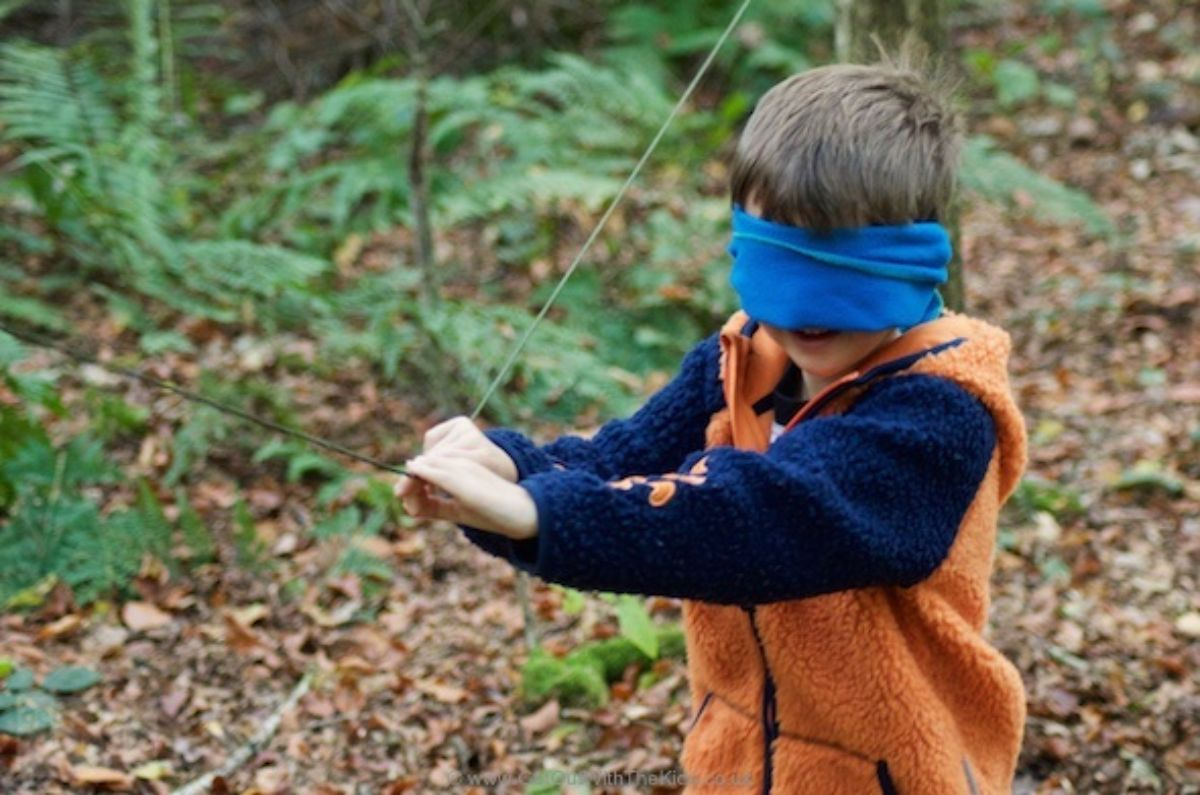 a boy stands in teh forest wearing a blindfold and holding a taut string