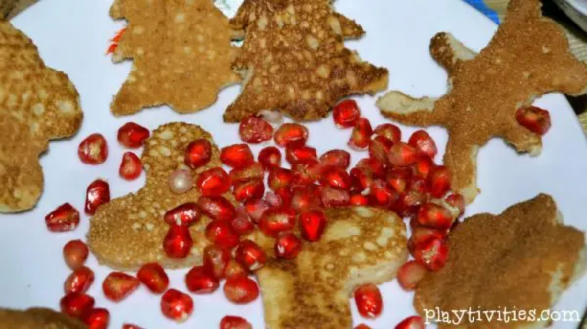 a plate of shaped pancakes scattered with pomegranate seeds