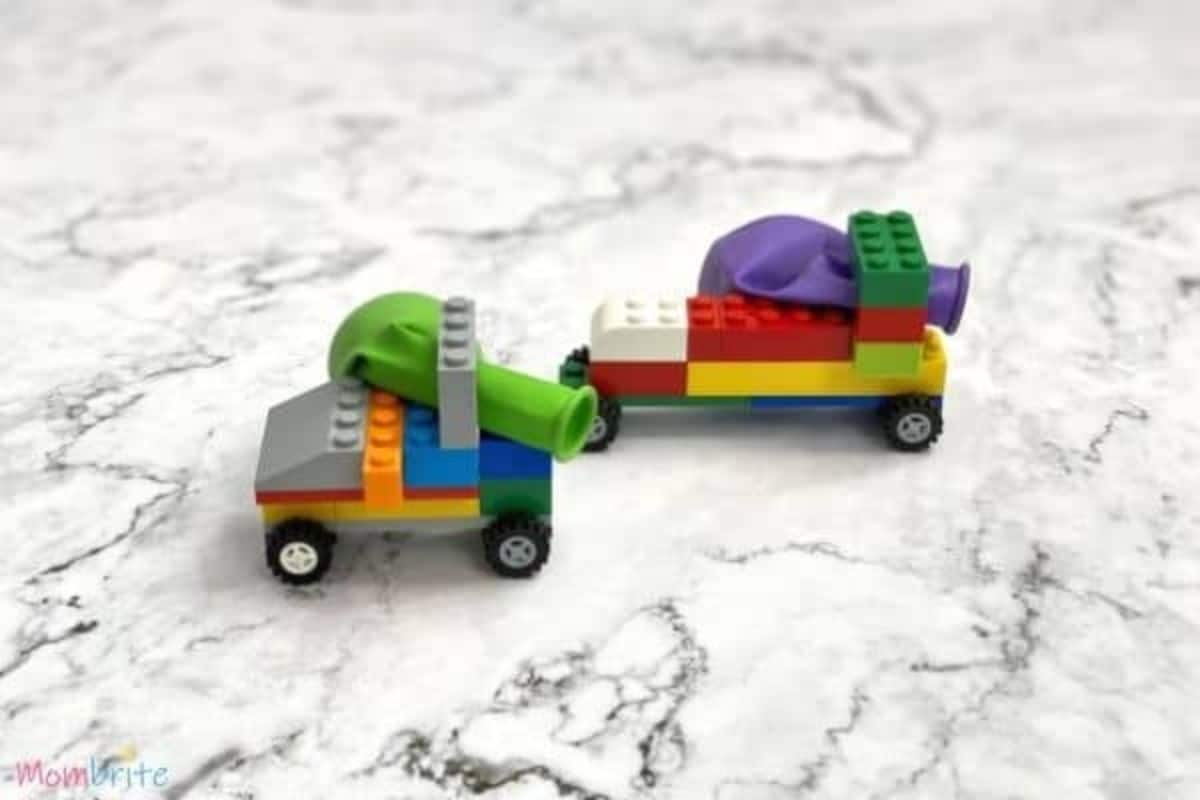 on a white marbled background are two lego cars with deflated balloons in the back of them