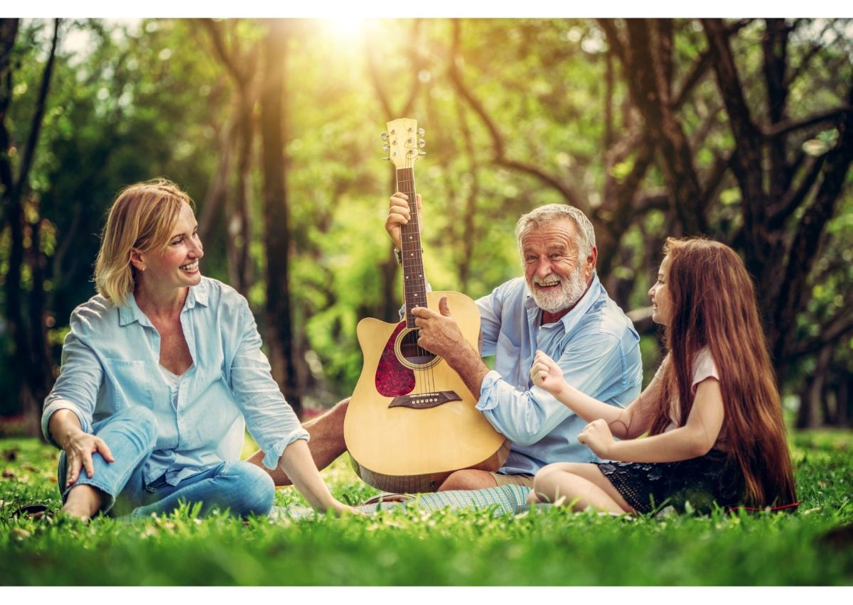 a woman, child, and man holding a guitar sit in a forest clearing at sunset