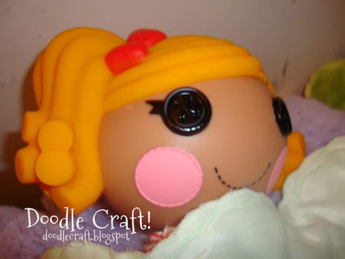 """A close up of a doll's face with yellow hair, large button eyes and pink cheeks. The text reads """"Doodle Craft! doodlecraft.blogspot"""""""