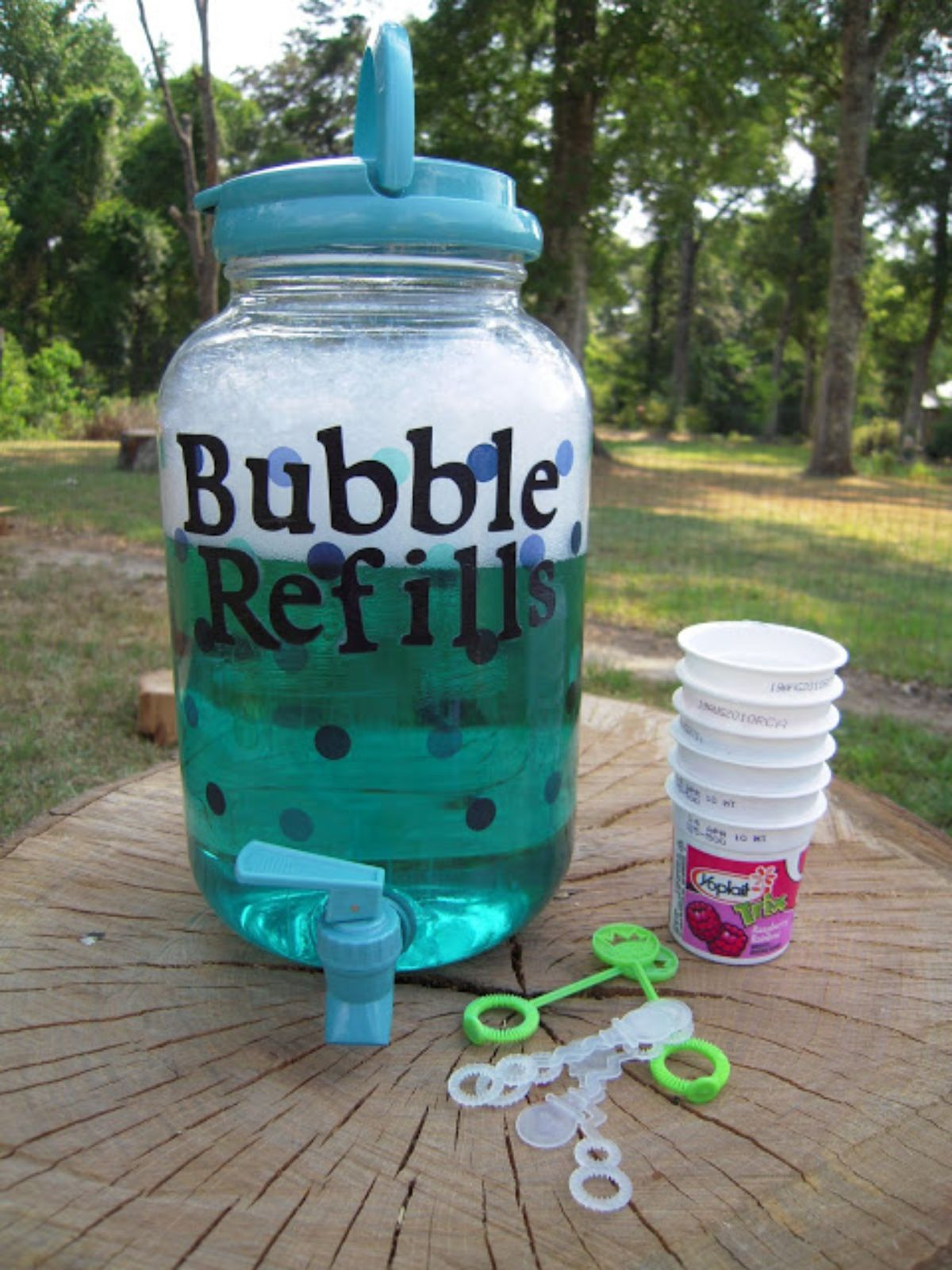 On a log top is a kilner jar full of bubble mixture, bubble wands and paper cups