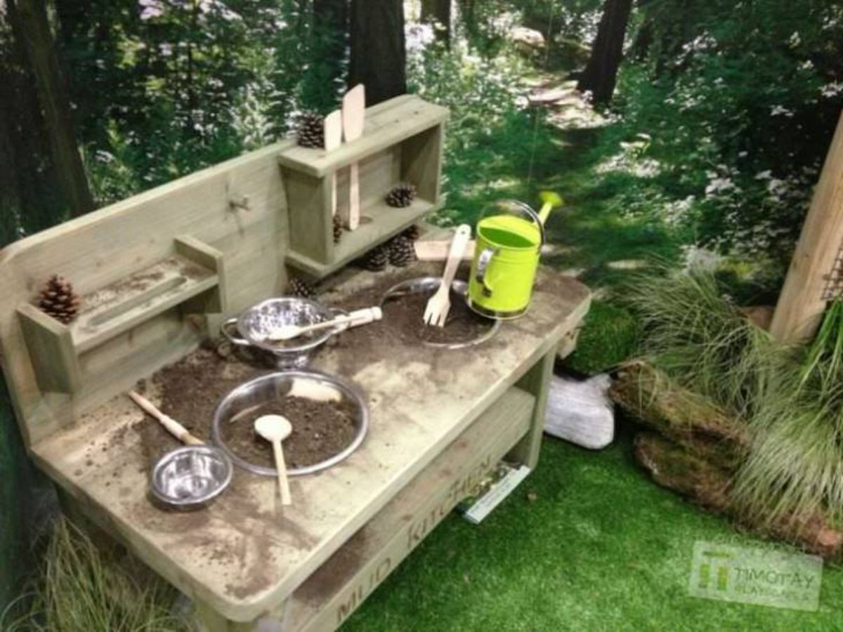 a mud kitchen made out of wood sits in a garden in front of some trees