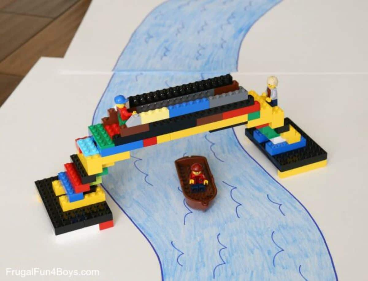 a lego bridge is put over the drawing of a river. A lego boat sails under it