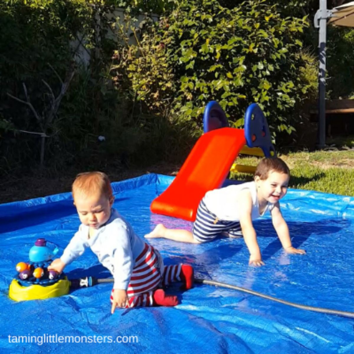2 toddlers play on some blue plastic filled with water from a hose. There is a red slide into the water