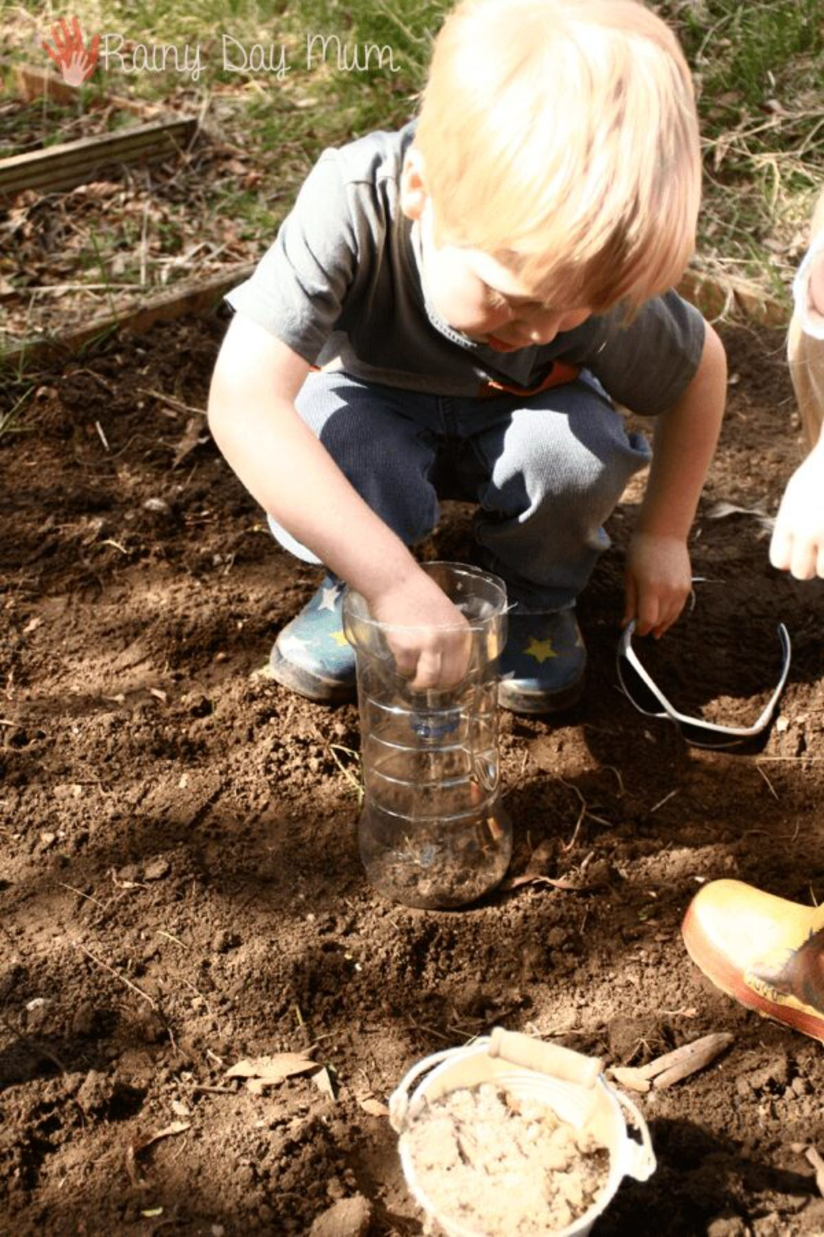 a boy digs in the dirt to fill up a plastic bottle