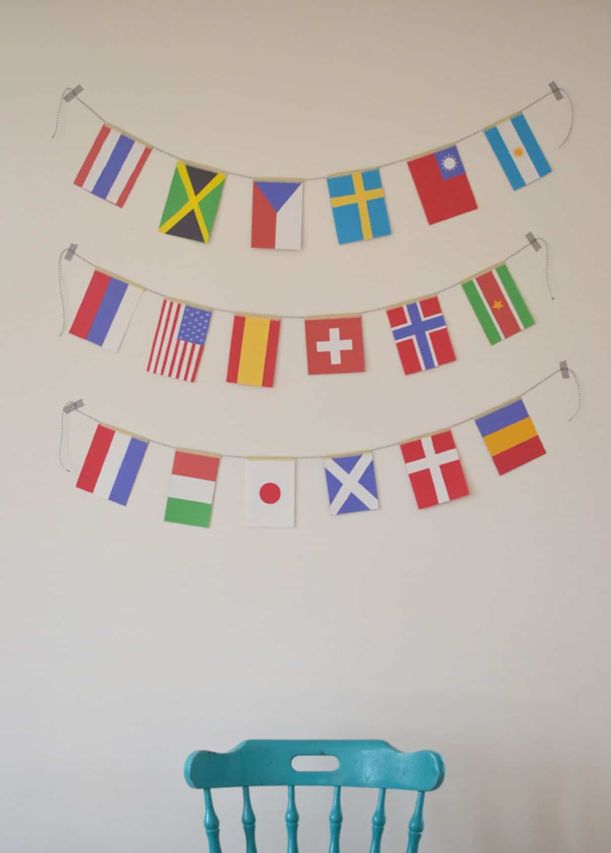 3 garlands of world flags hang on a wall above a blue chair