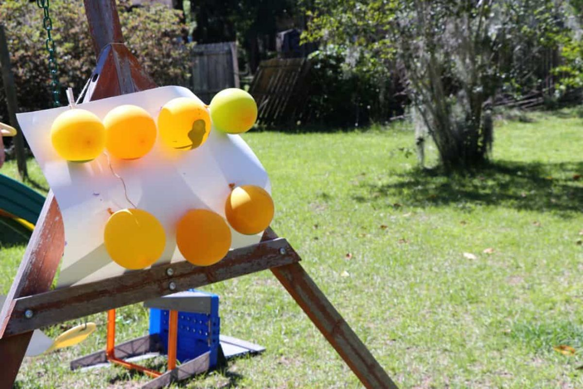 an easle is in a graden with a piece od paper with 7 orange balloons fixed to it