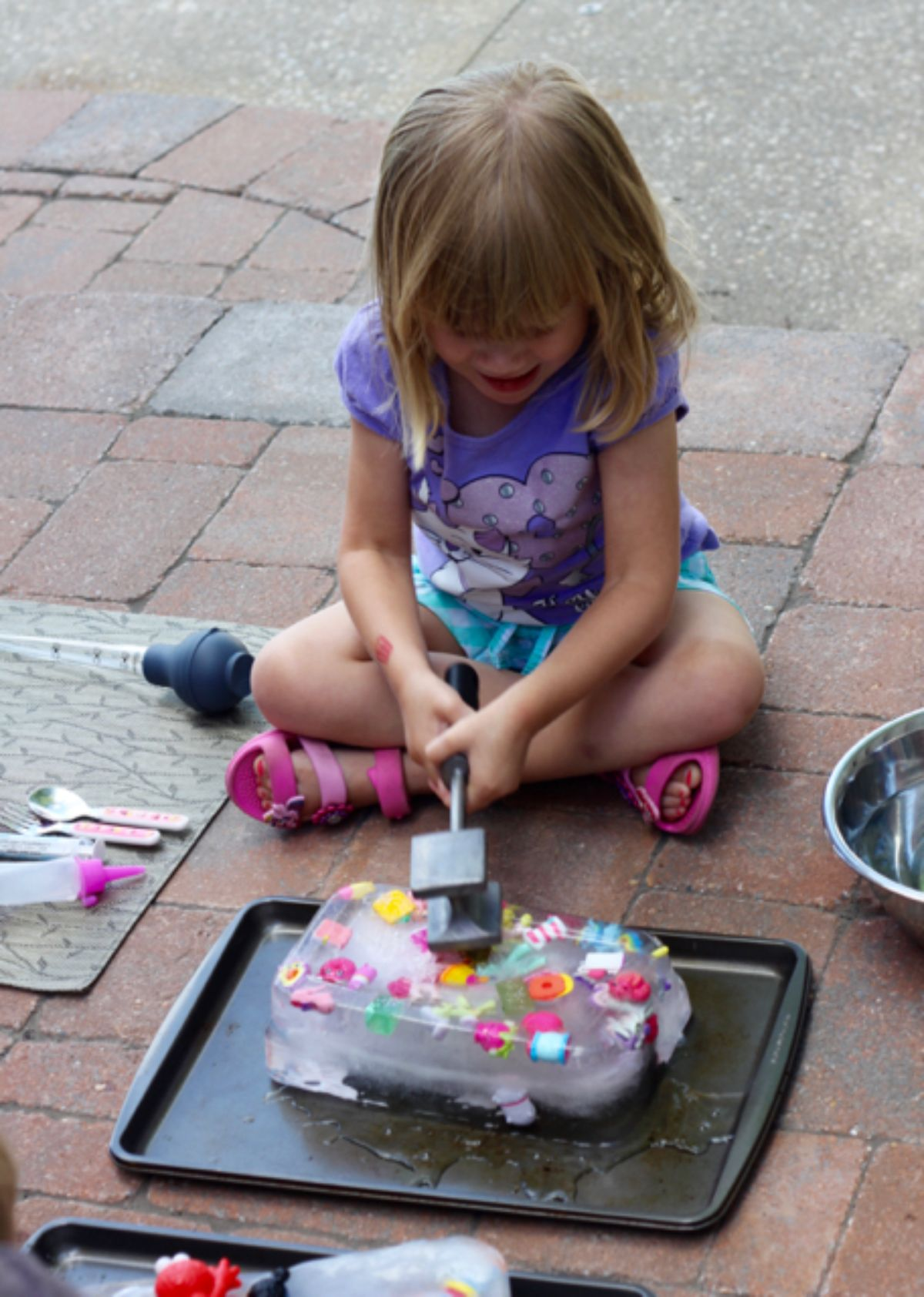 a girl sits on the floor on the backyard. In front of her is a tray with a giant ice block filled with small colorful toys
