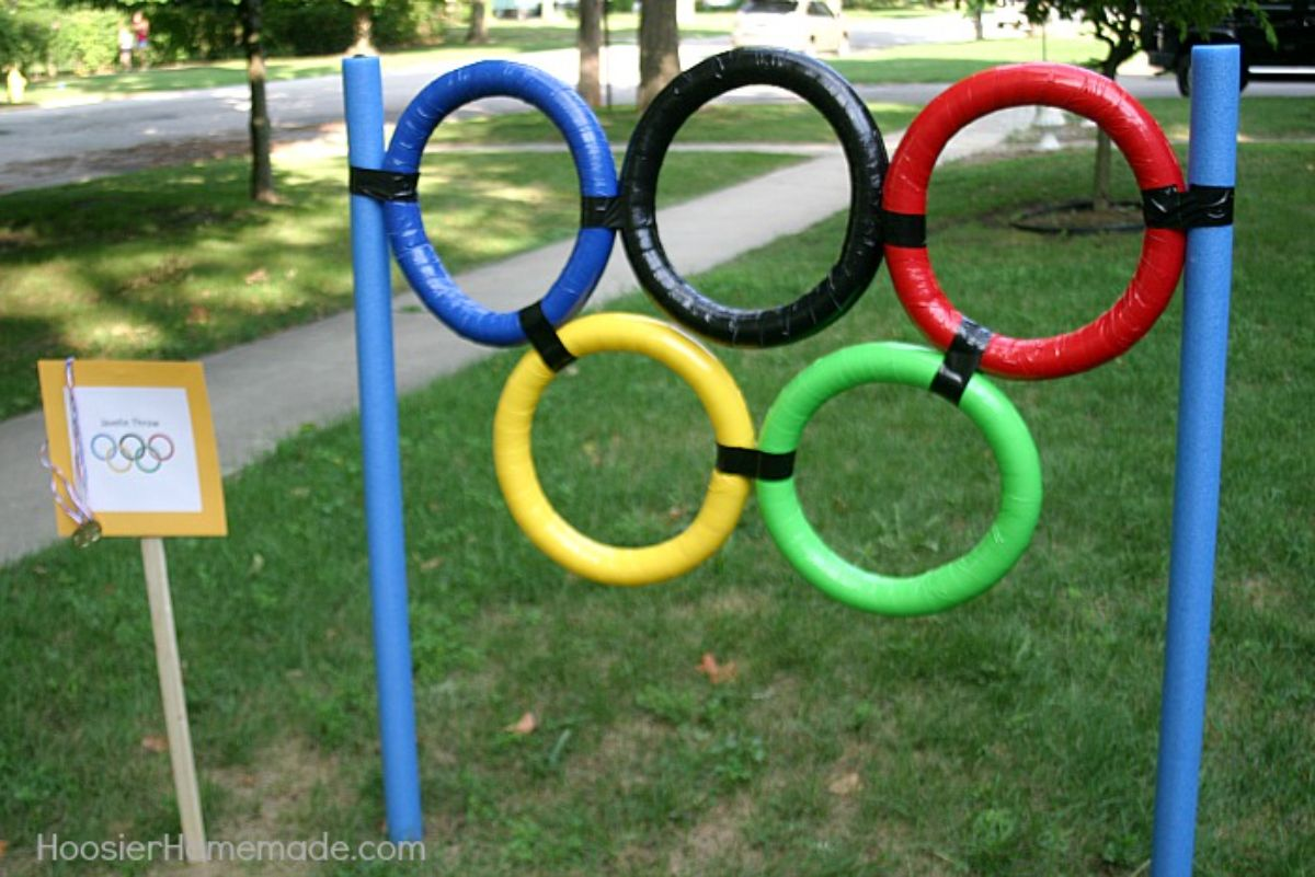 Standingi n a front yard are the olympic rings supported on two pool noodles