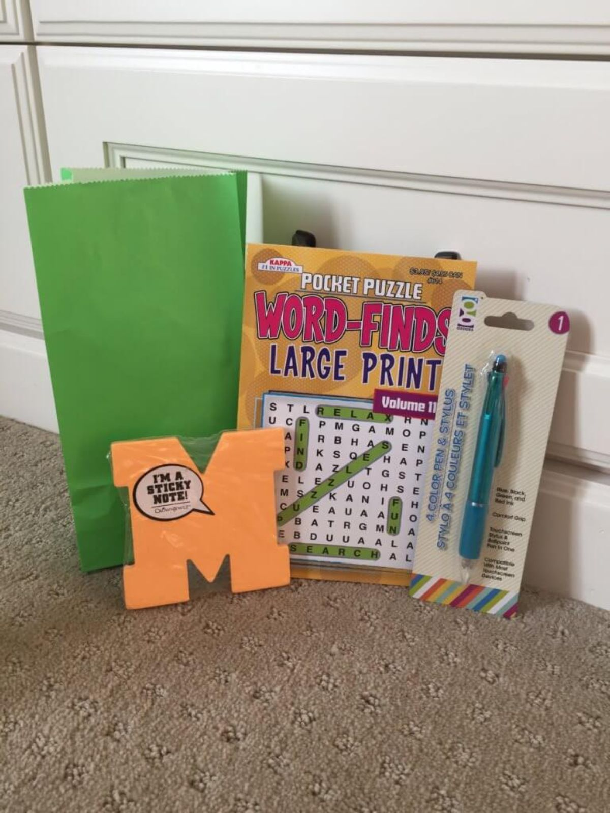 on the floor in front of a door is a green paper bag with a pocket puzzle, pen and sticky notes in front