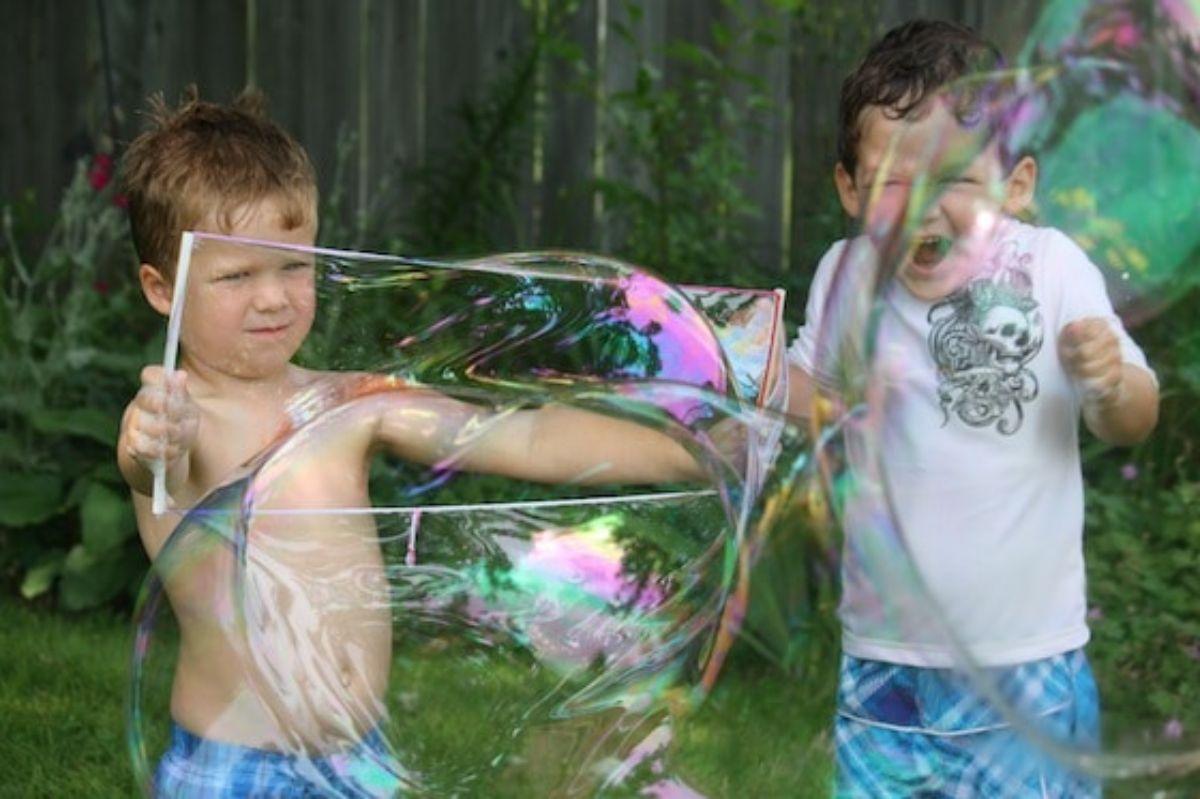 2 boys make giant bubbles in a garden