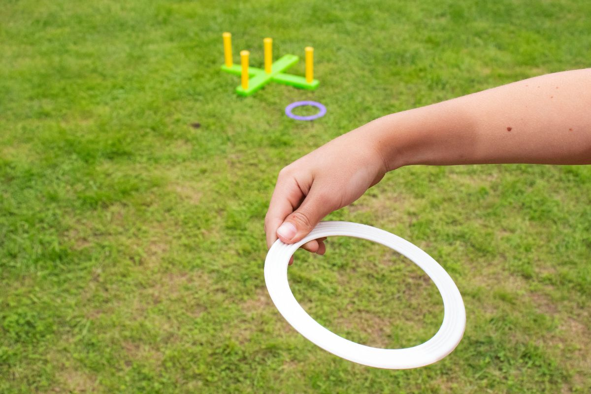 a hand tosses a ring toward some pins on the grass