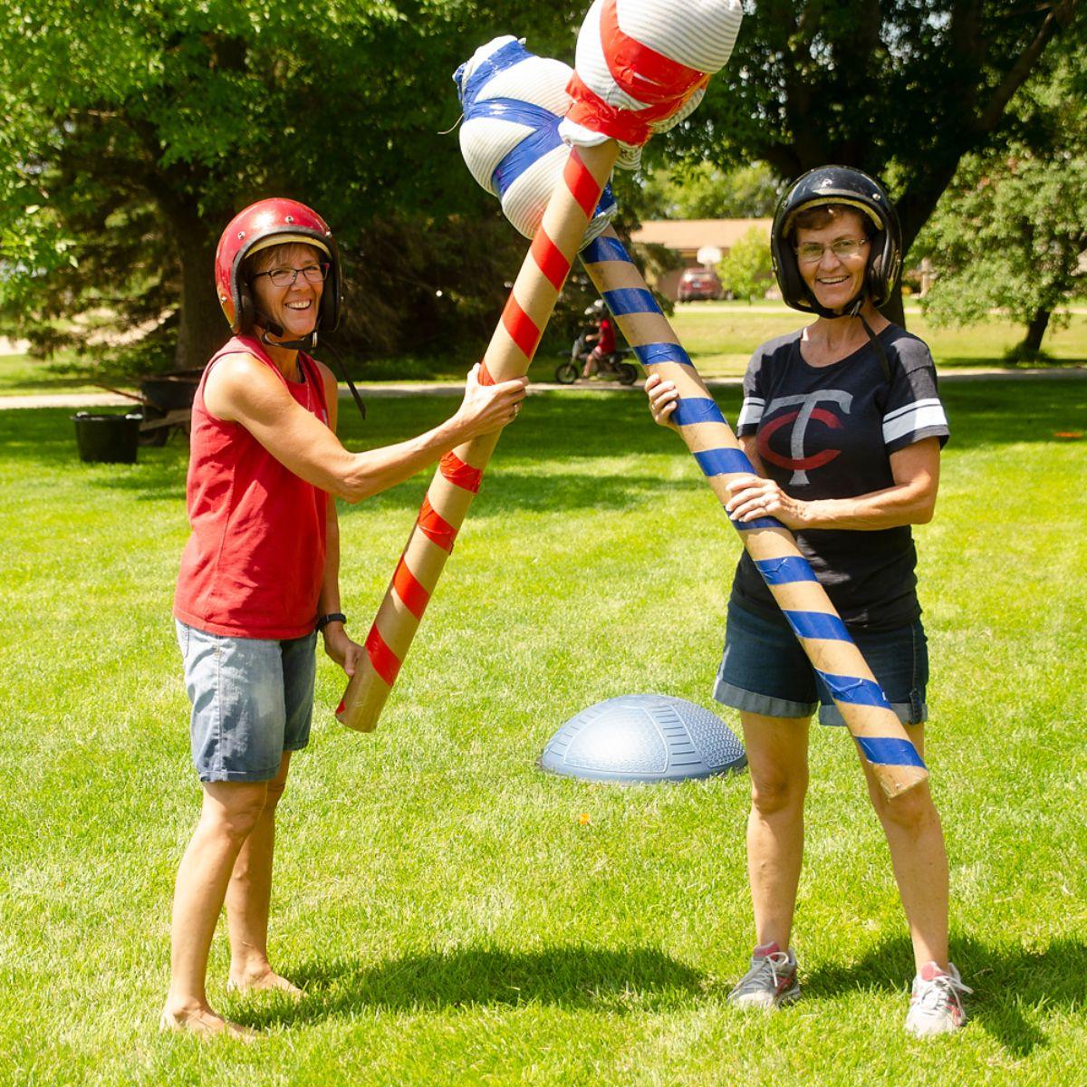 two women in crash helmets hold giant jousting sticks