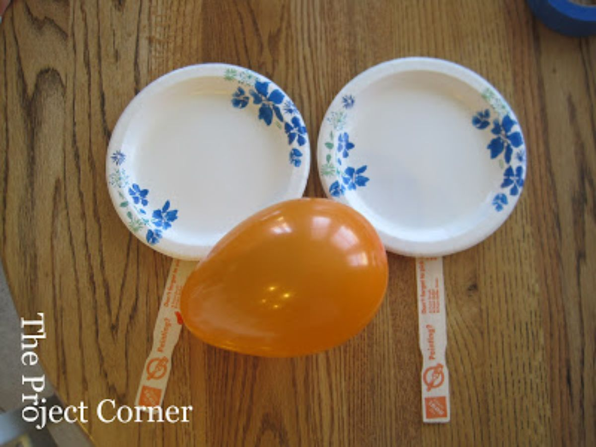 on a table are 2 paper plate paddles and a balloon