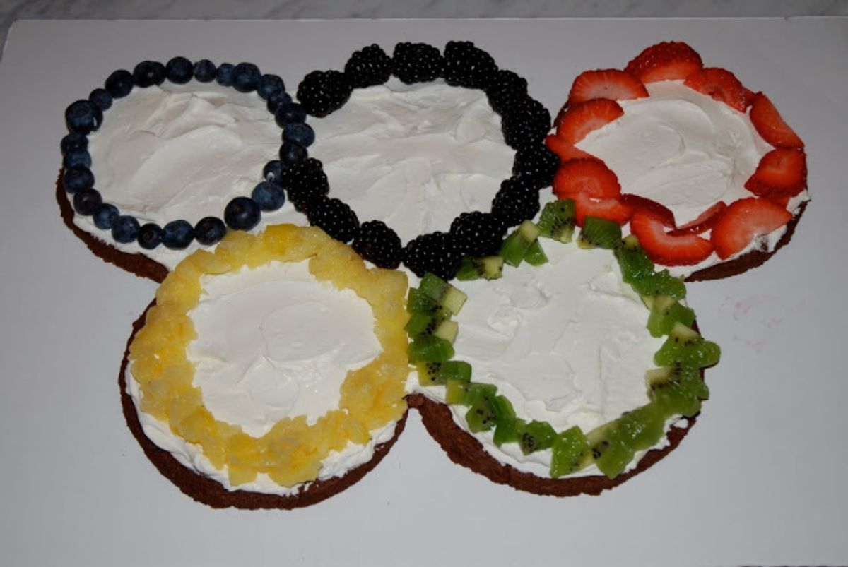 olympic rings made out of cookies, cream and different fruits