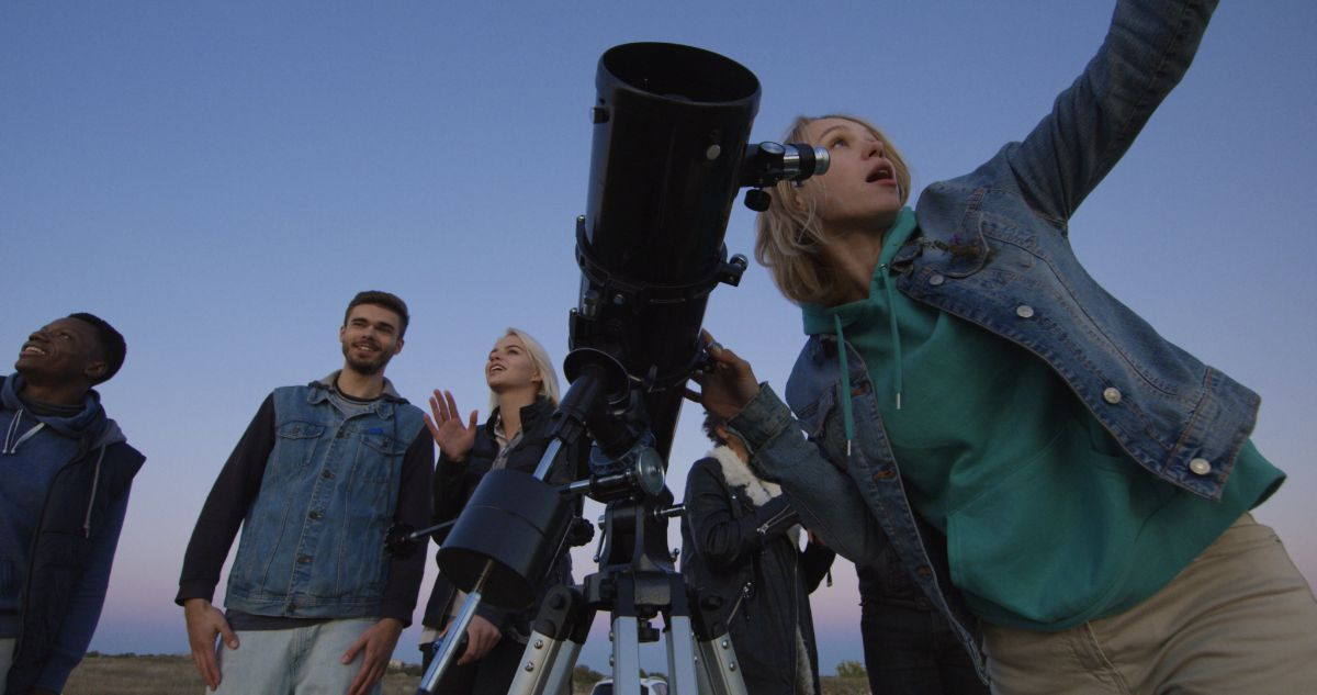 a familly stand in front of a darkening sky with a telescope