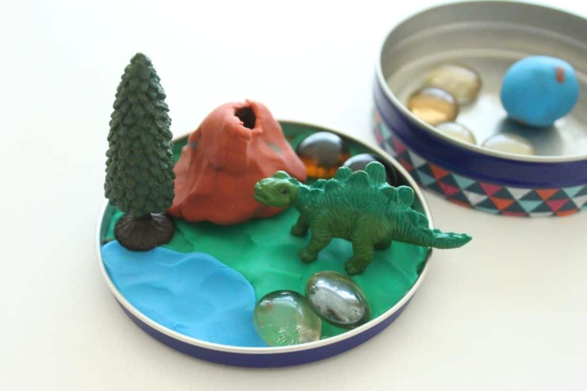 the lid of a small tin has been covered with blue and green playdough. Sitting on that is a toy dinosaur, a tree and a volcano