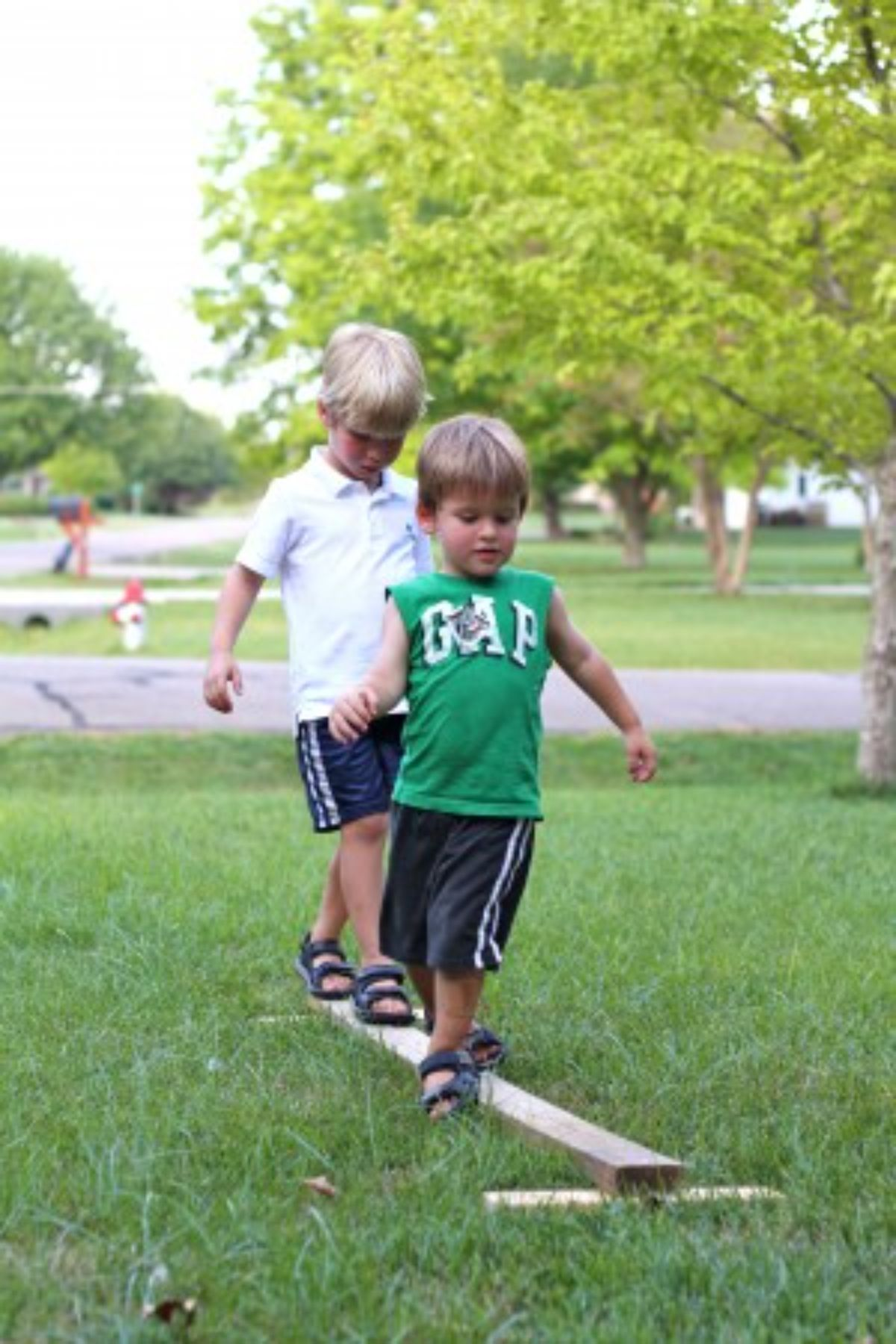 2 boys walk along a balance beam in a front yard