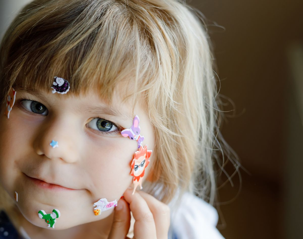 a small girl is looking at the camera with stickers all over her face