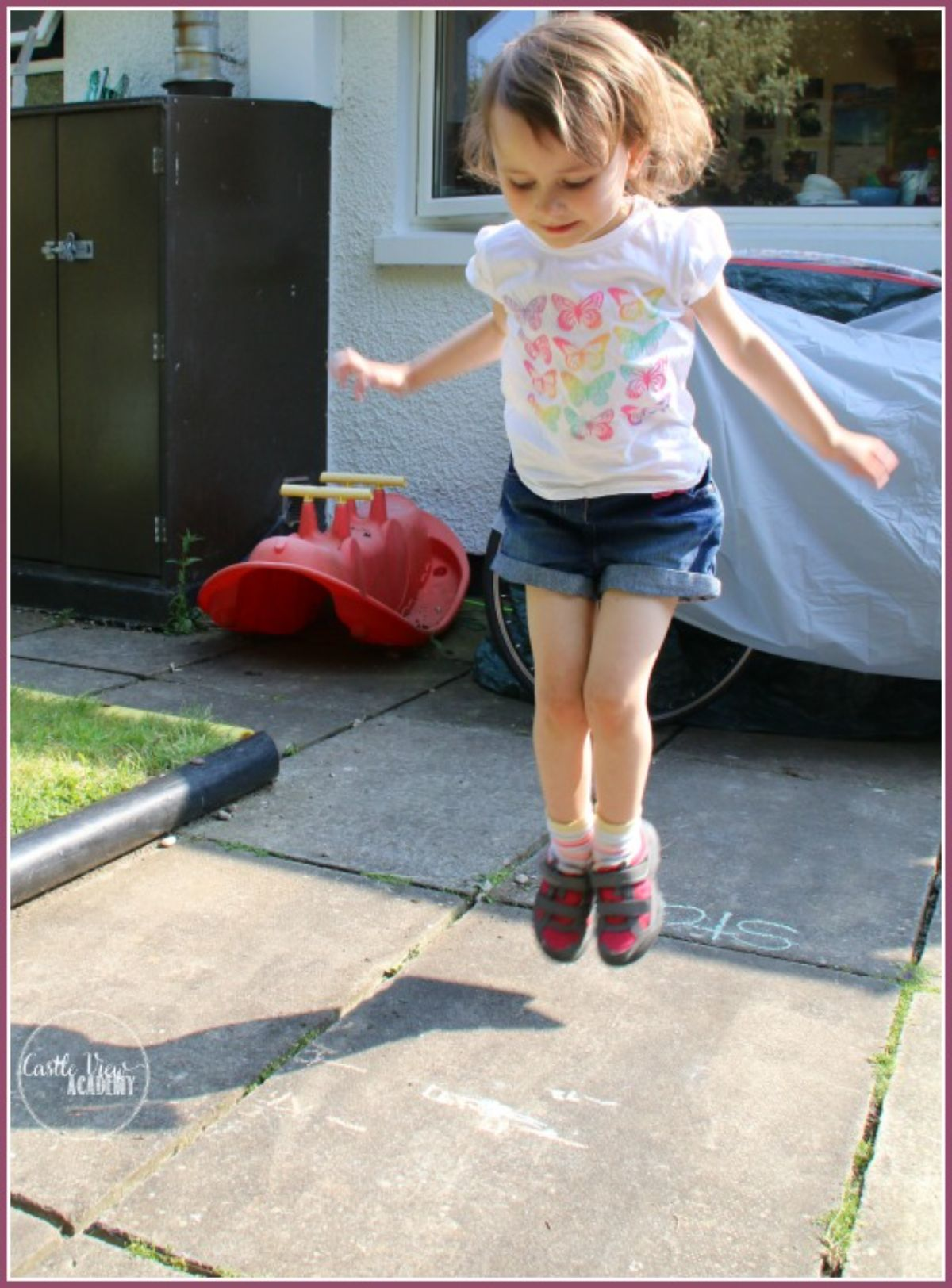a girl jumps in the air in a yard