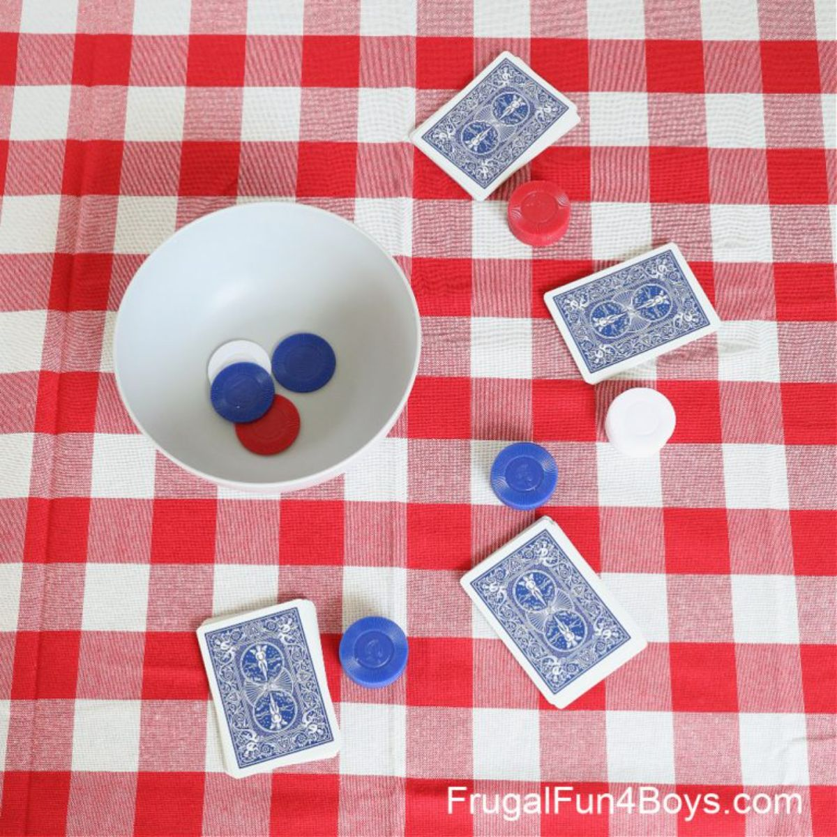 on a checked tablecloth is a white bowl full of plastic coins. 4 playing cards lay face down