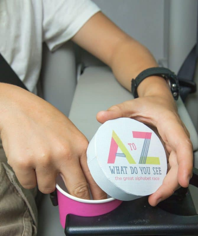 """hands reach into a paper cup, holding a lid that reads """"A-Z what do you see: the great alphabet race"""""""