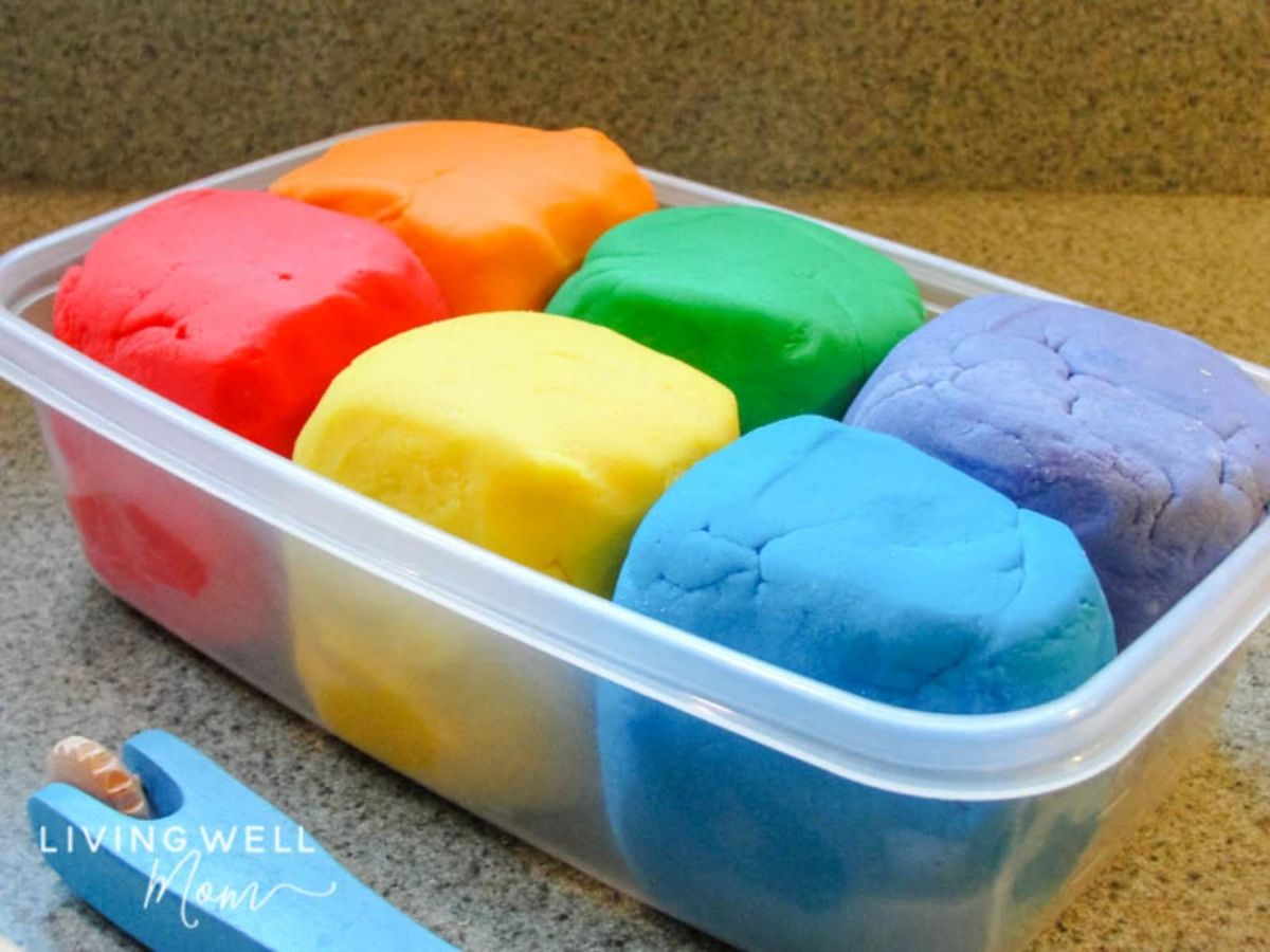 a tupperware box sits on a table filled with 6 different colors of playdough