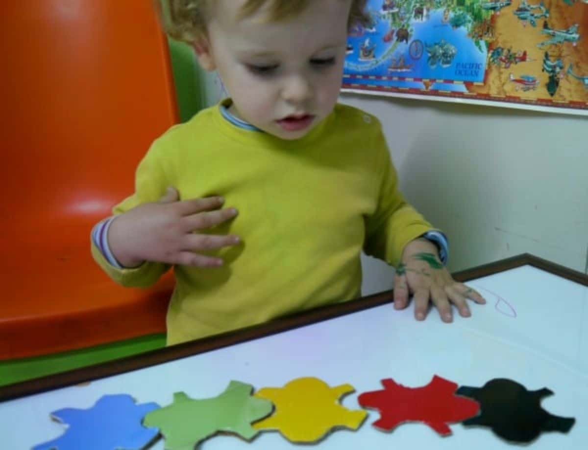 a toddler looks down at some colored jigsaw pieces on a table