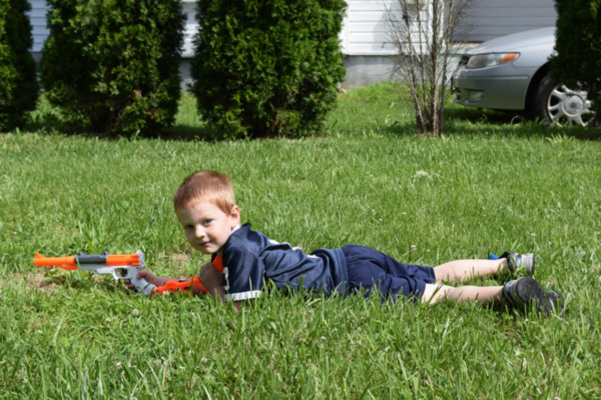 a boy lays on his front in the grass, holding a nerf gun