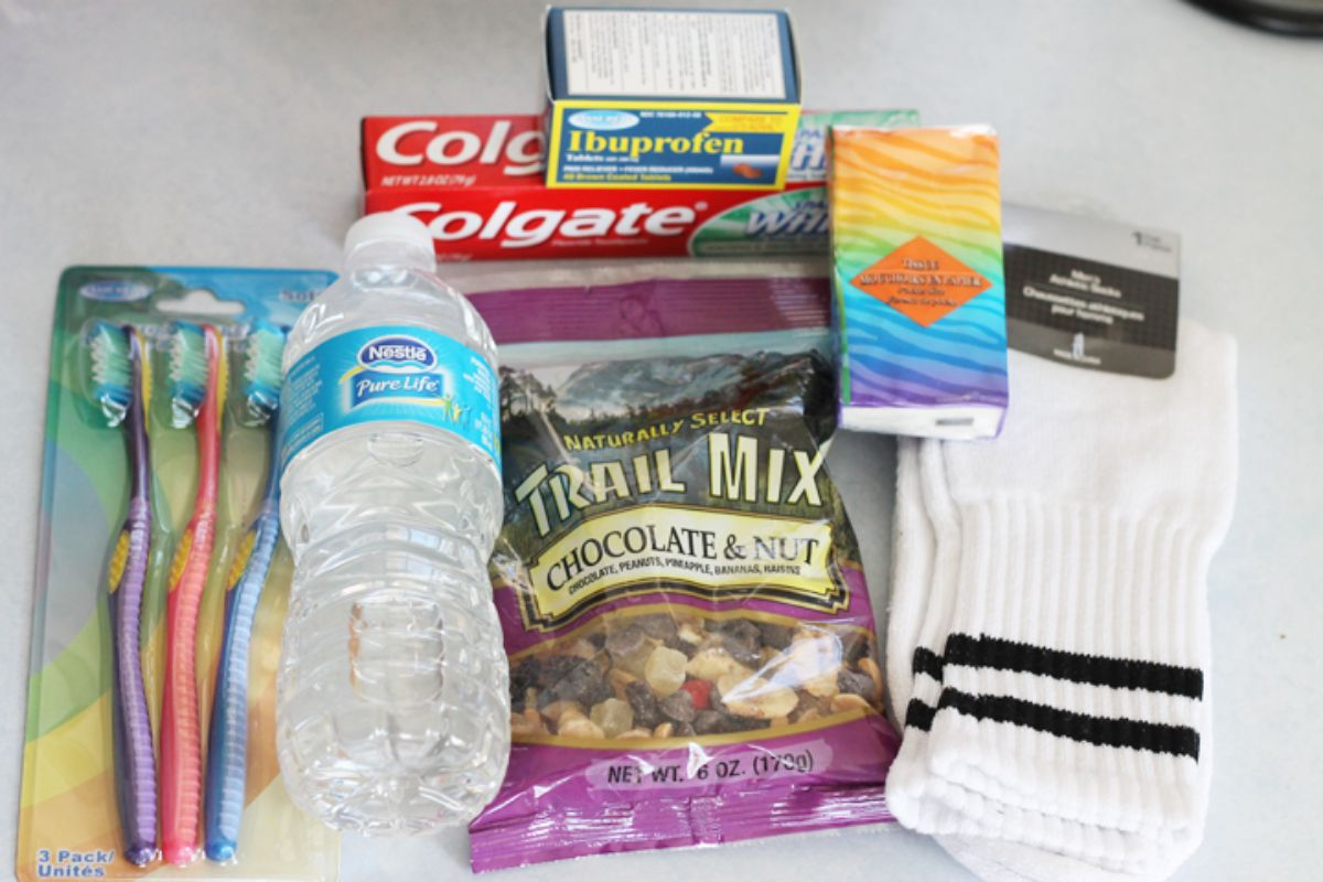 on a table are toothbrushes, a bottle of water, trail mix, socks, tissues, toothpaste, and ibuprofen