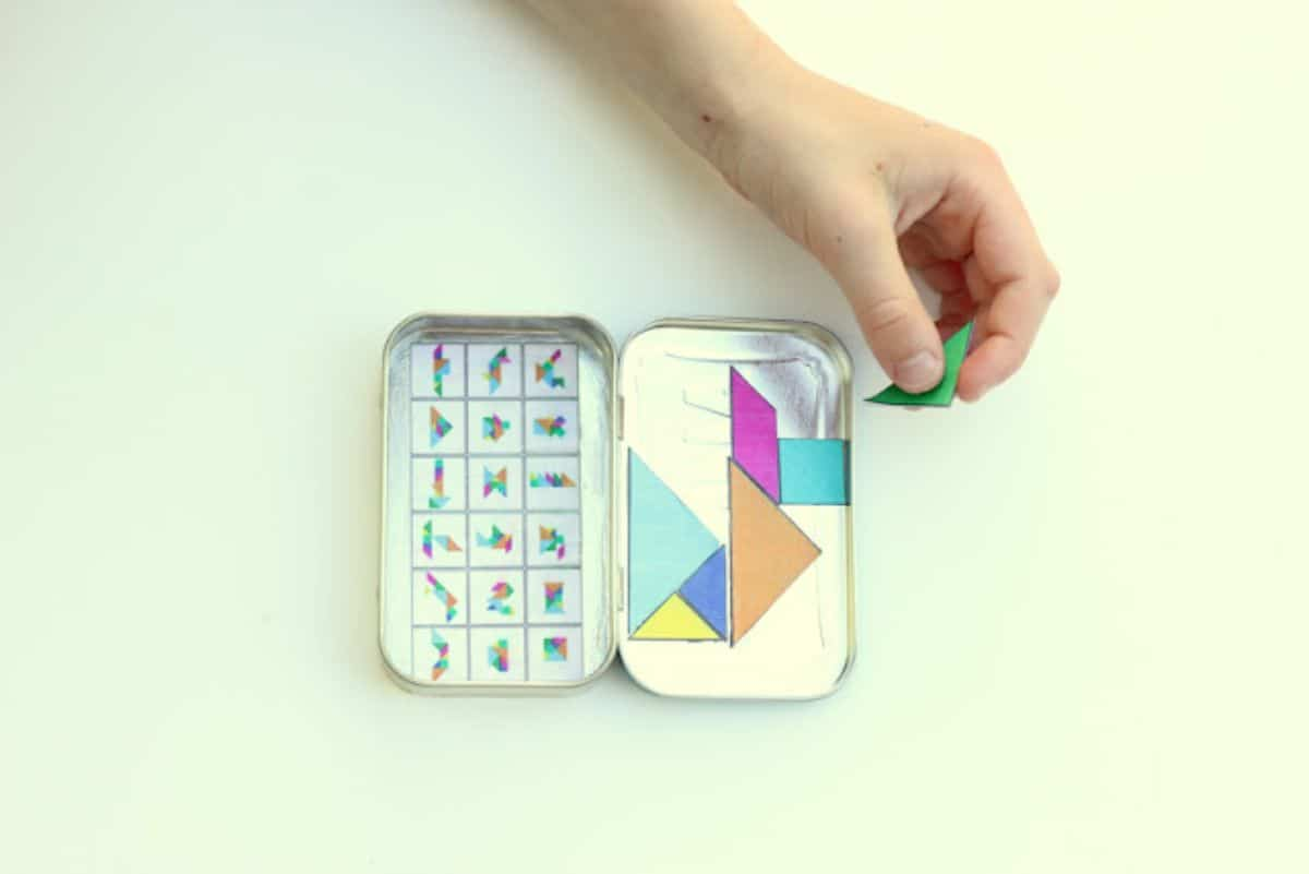 a hand holds a green paper triangle. underneath is a rectangular tin filled with tangram pictures