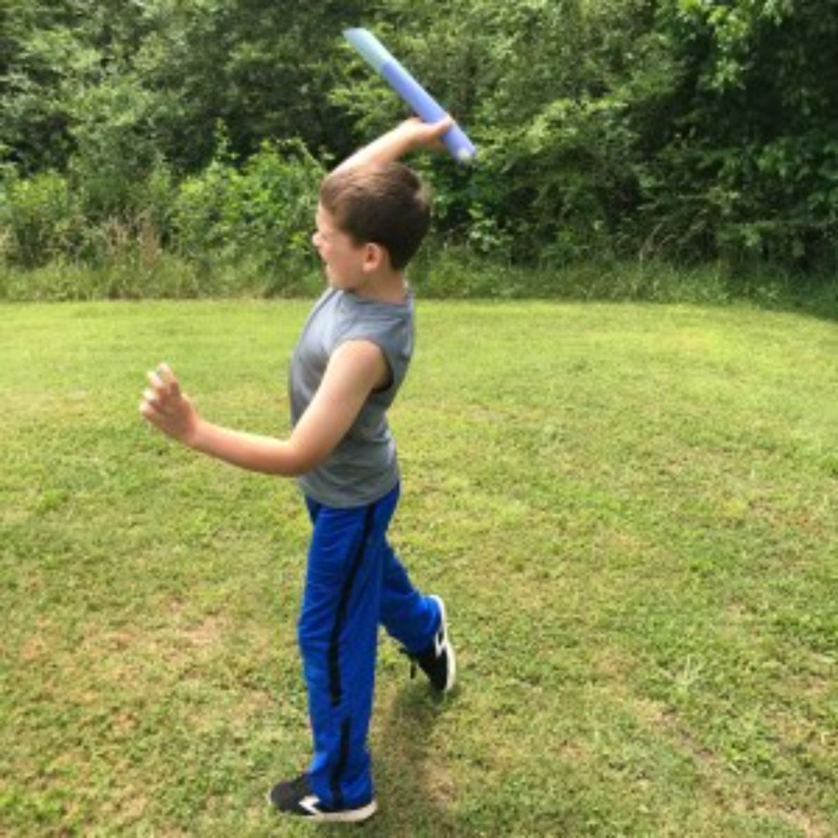 a boy holds a paper javelin in the air as if to throw it