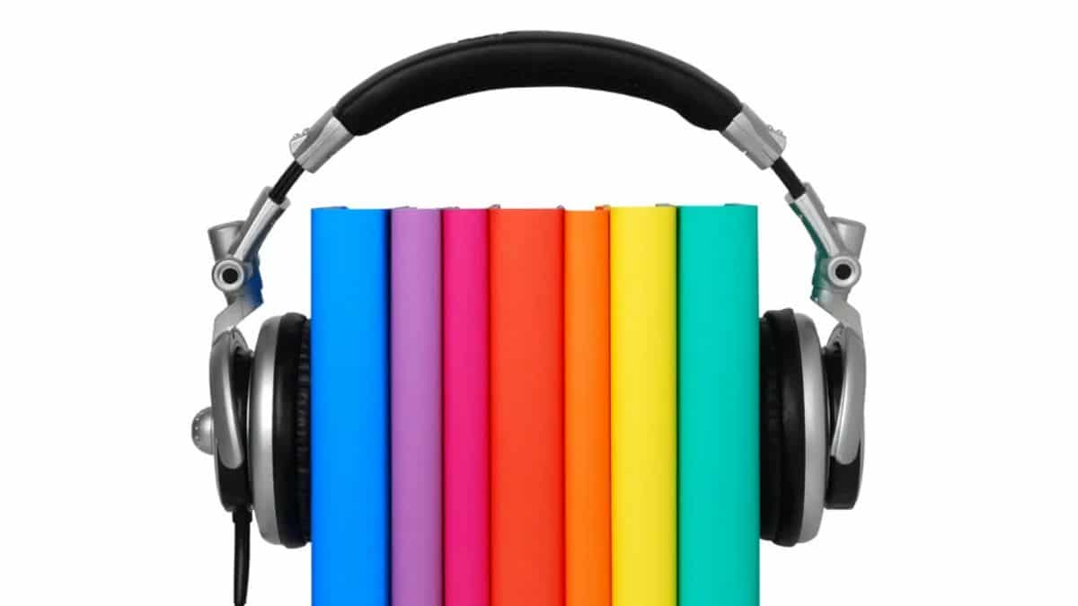 headphones are resting over 7 books in rainbow colors
