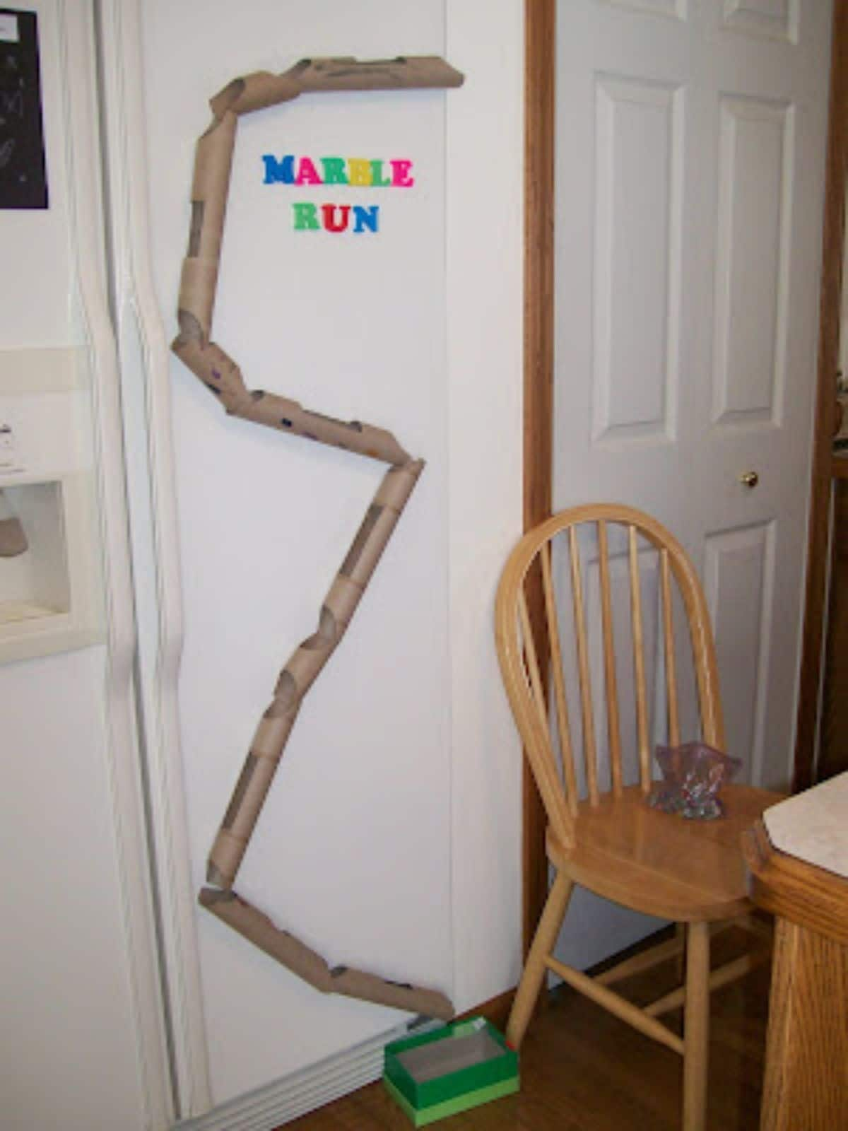 a marble run has been fixed to a wall in a room made of cardboard tubes