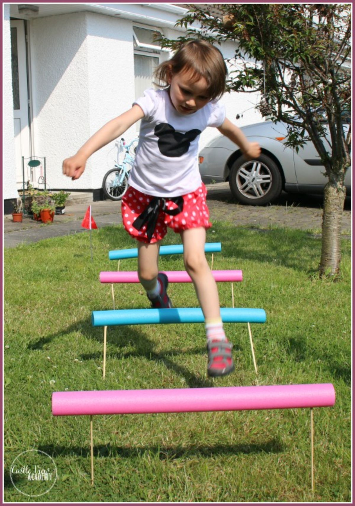 a girl jumps over hurdles made of pink and blue pool noodles