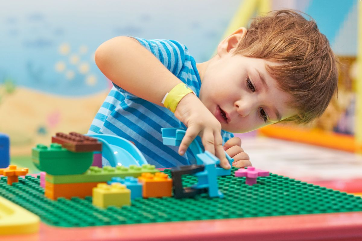 a young boy sits in front of a table covered in lego bases. He is fixing duplo to the top