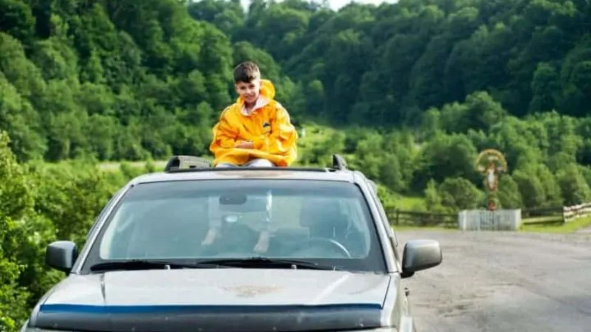a child in a yellow jacket sits on top of the roof of a blue car in a street
