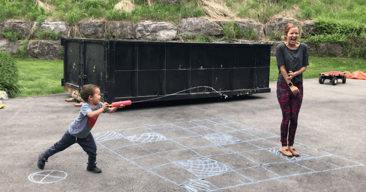 a mom stands in a backyard while a small boy shoots her with a water pistol. On the floor is a chalked square pattern