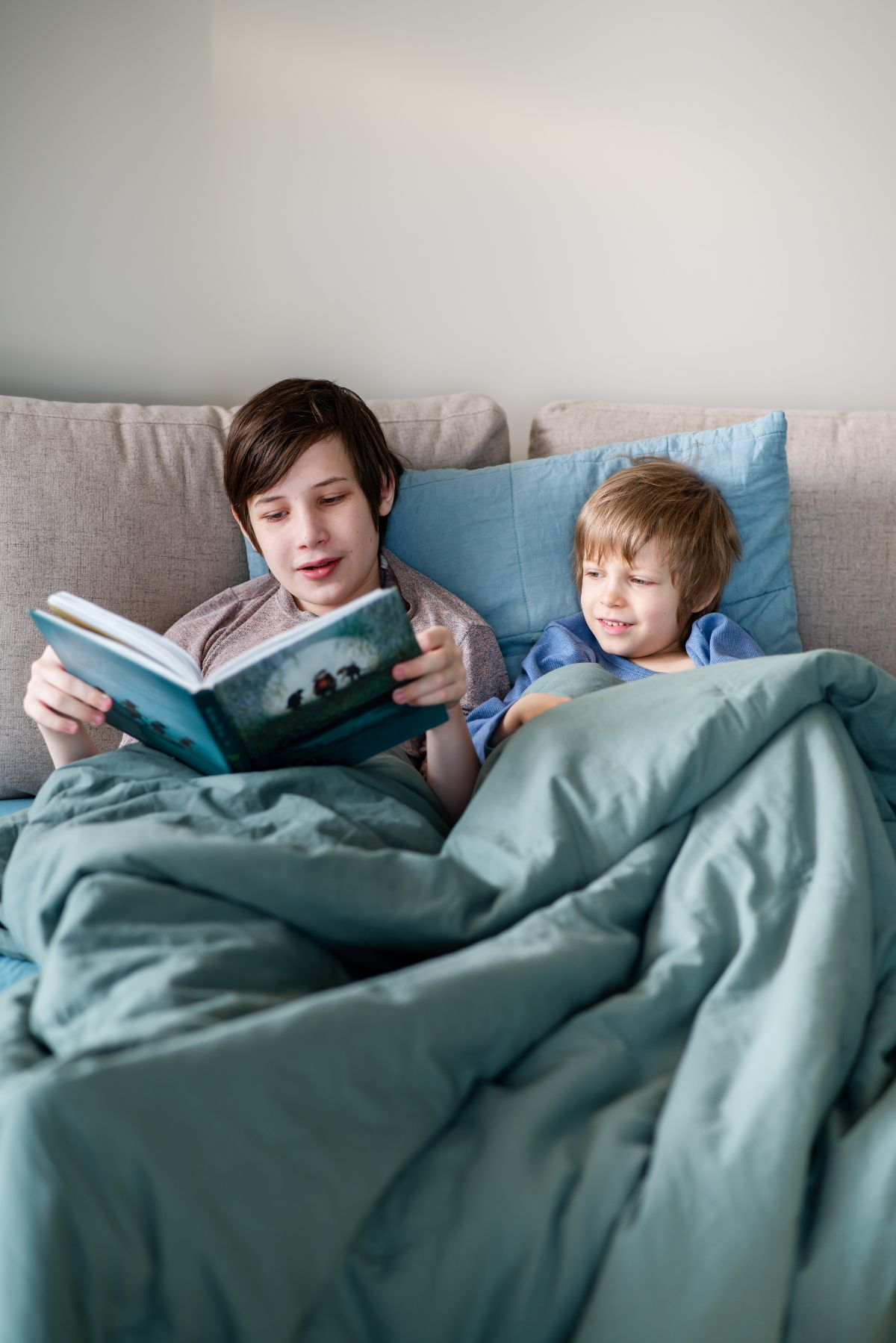 two brothers sit under a comforter reading a book