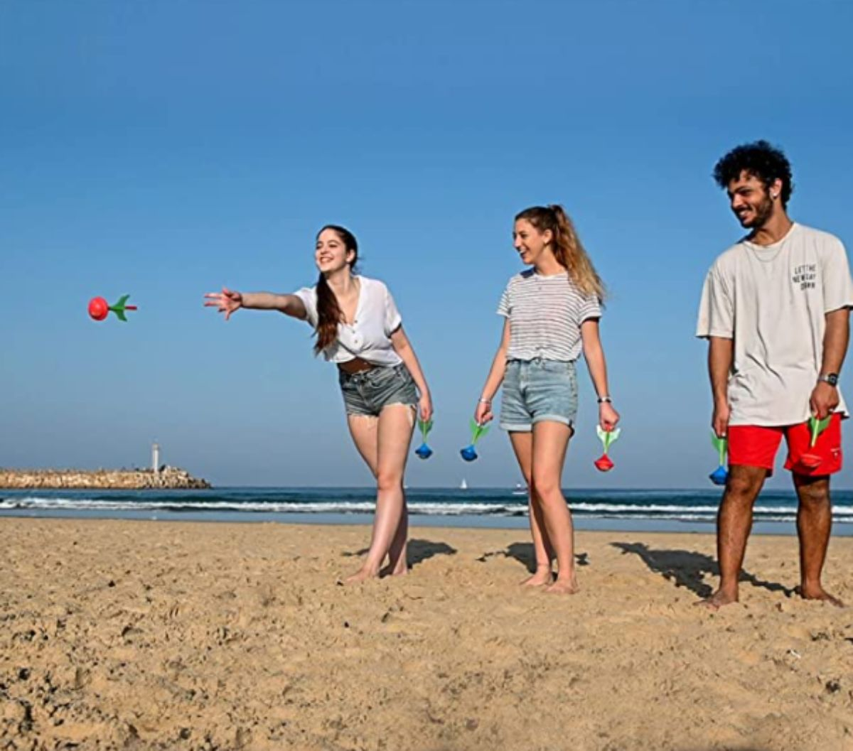 2 teen girls and a boy stand on a beach throwing lawn darts