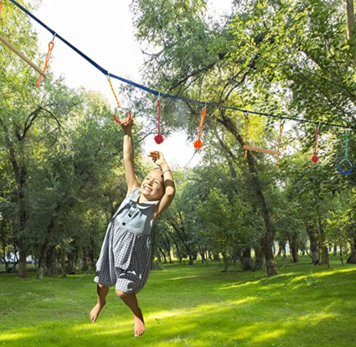 a girl in a checked dress hangs from some monkey bar rings in a garden