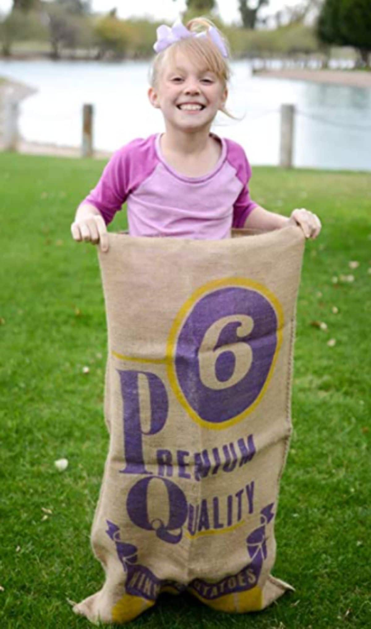 a girl stands in a potato sack on some grass