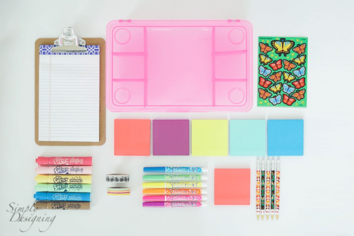 alid out on a surface is a clip board with pad, marker pens, a pink storage box, stickers, post it notes and pencils
